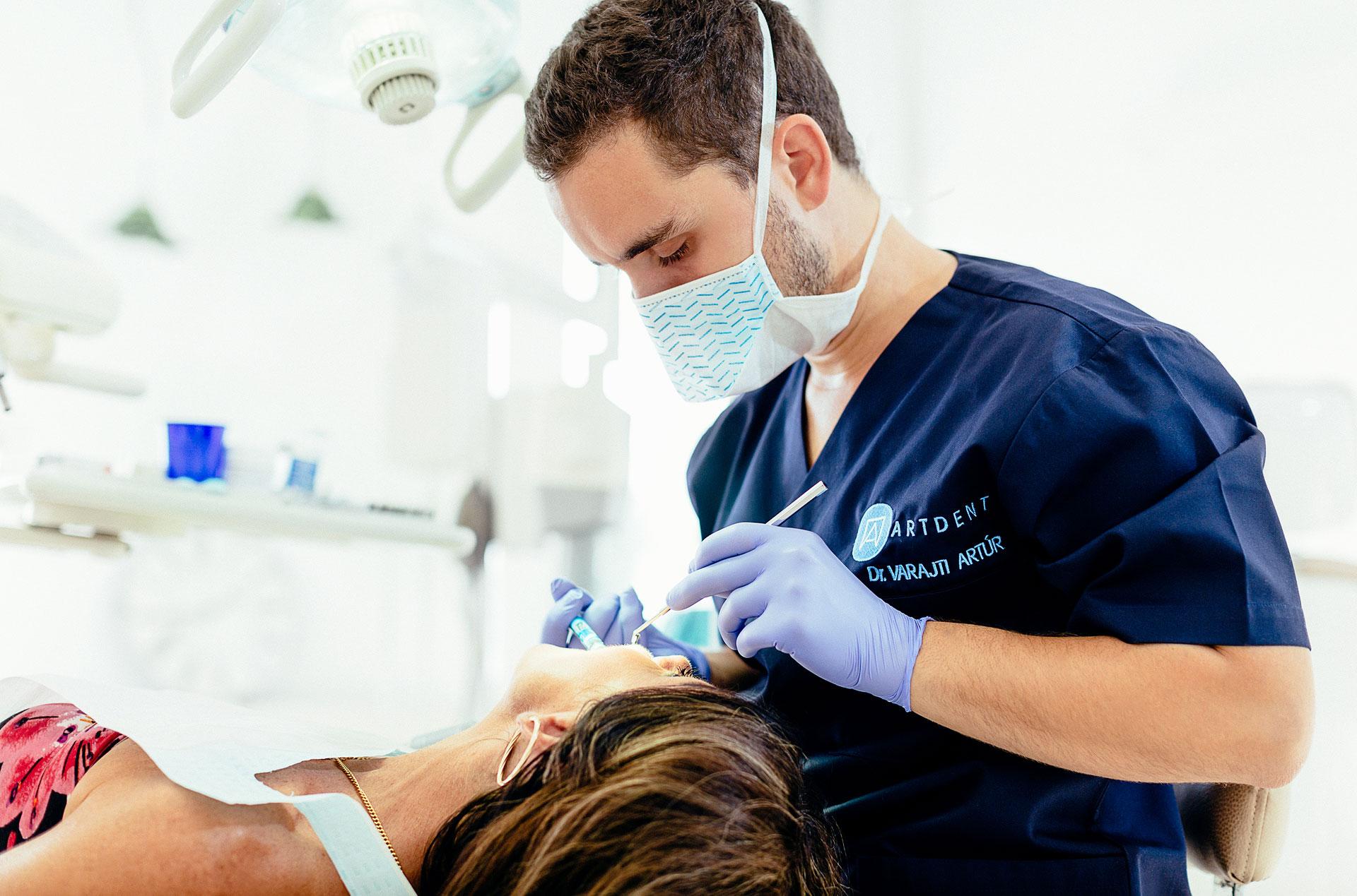 A budapesti fogászati rendelőben a szájsebész implantációs műtét előtt érzéstlenítőt ad a páciensnek.