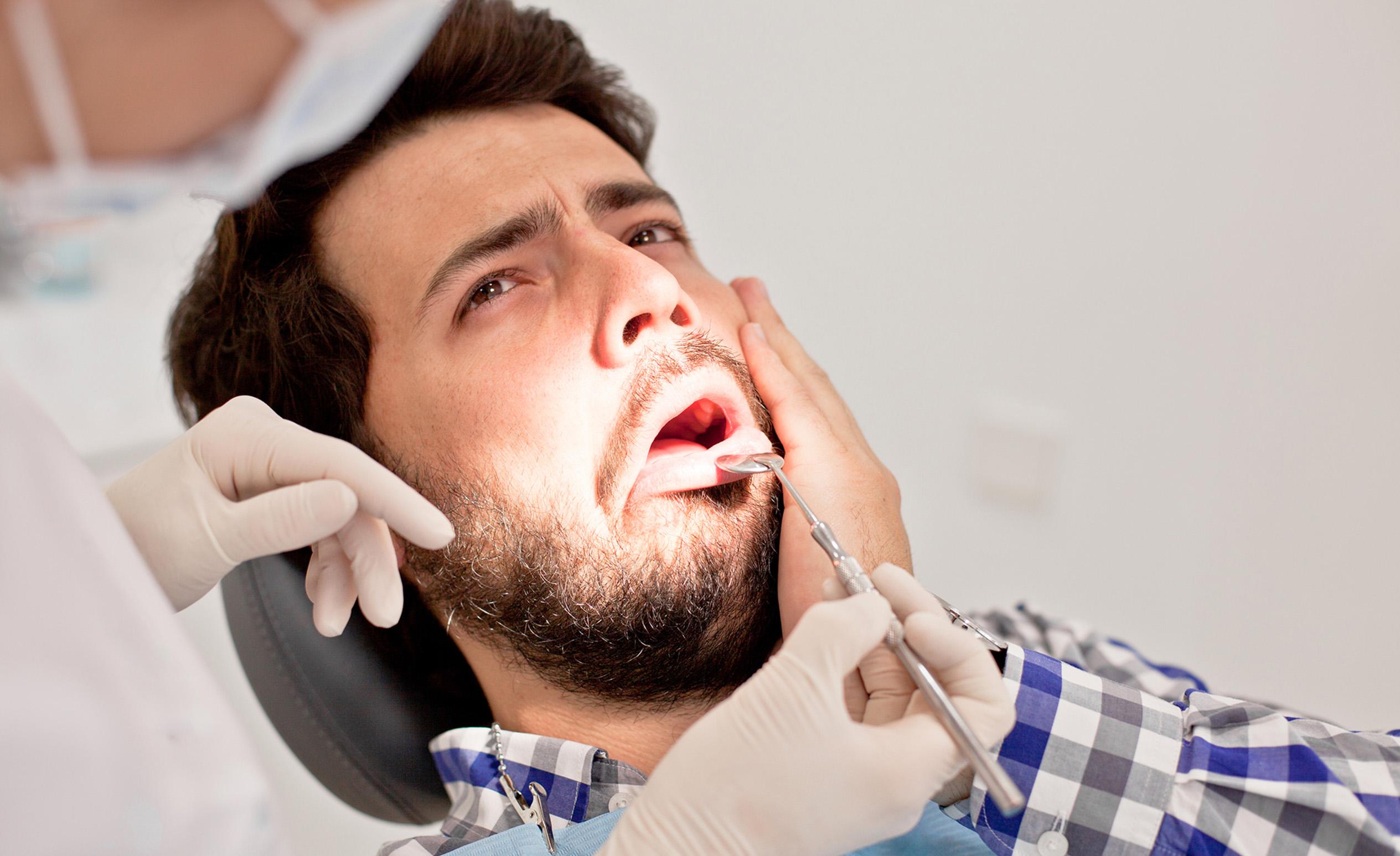 Fogorvos vizsgál egy férfit, aki fogja a fejét érzékeny foga miatt.