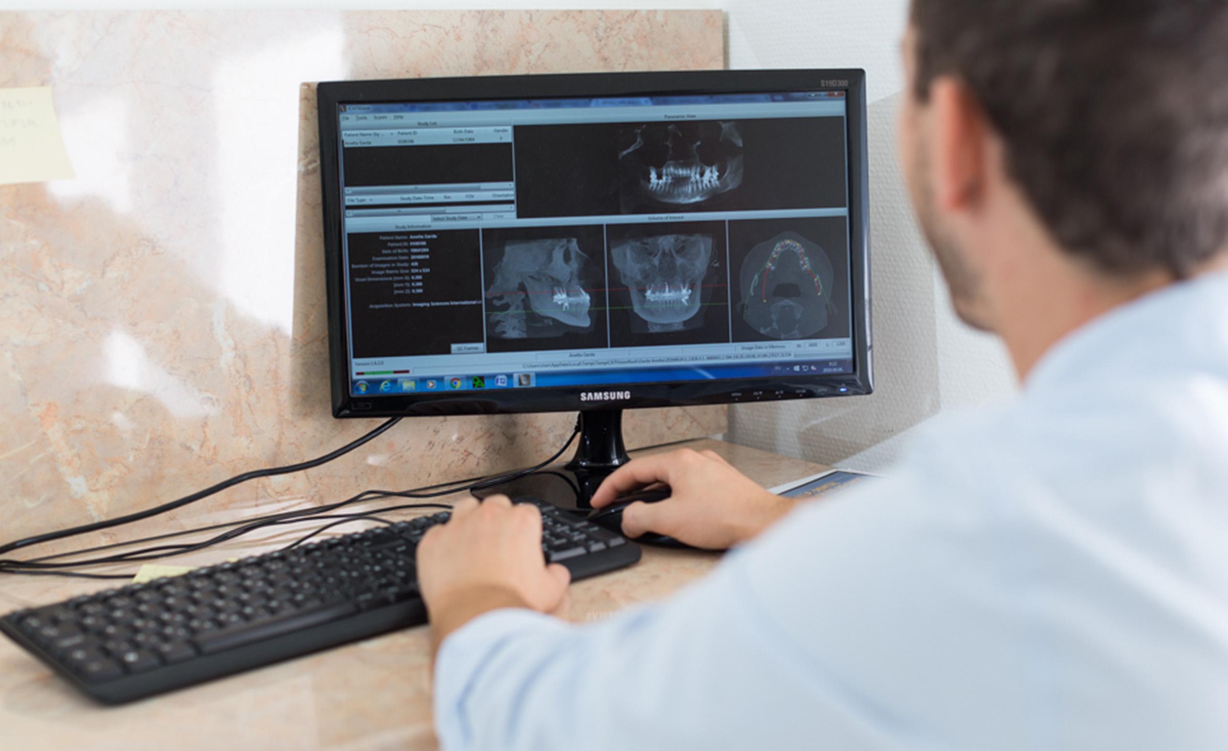 Dr. Varajti Artúr budapesti fogorvos, szájsebész ül a számítógép előtt és fogbeültetést támogató programot használ.