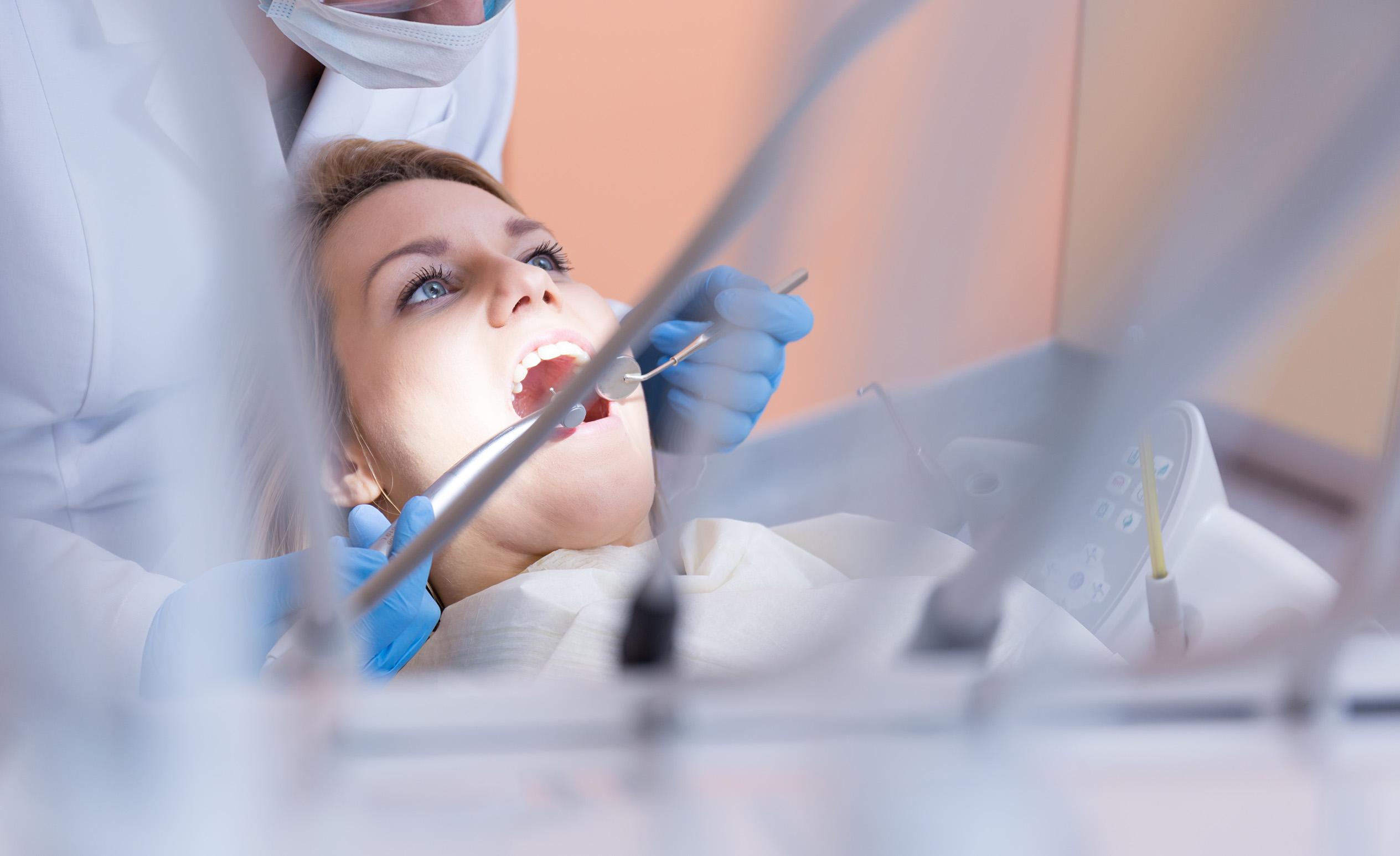 Fúrjak egy kék szemű nőnek fogát a budapesti fogorvosi rendelőben.