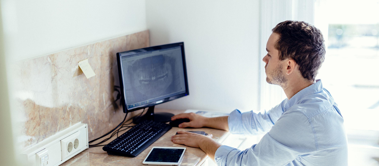 Csontpótlás előtt Dr. Varajti Artúr szájsebész nézi a monitort a budapesti fogászaton.