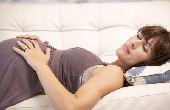 Terhes nő alszik az ágyon, közben fogja a hasát.