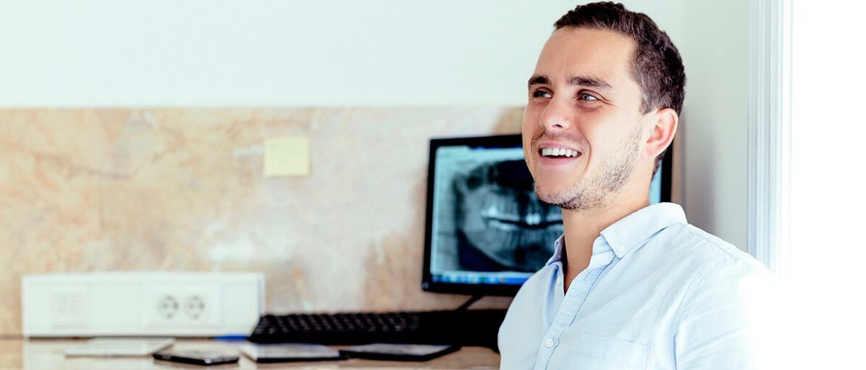 Dr. Varajti Artúr fogorvos, szájsebész ül és mosolyog.