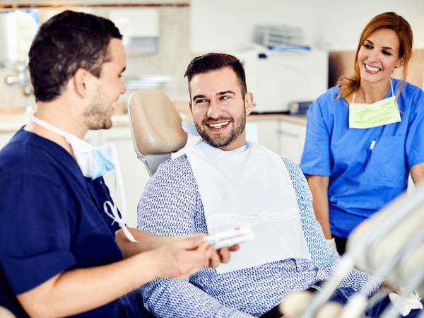 Dr. Varajti Artúr fogorvos és szájsebész és páciense beszélget fogkőeltávolítás után.