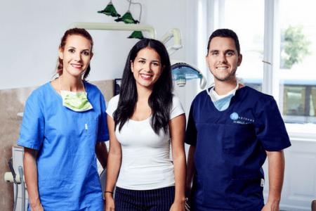 Dr. Varajti Artúr fogorvos, fogászati asszisztens és páciens állnak egymás mellett és mosolyognak a bölcsességfog eltávolítás után.