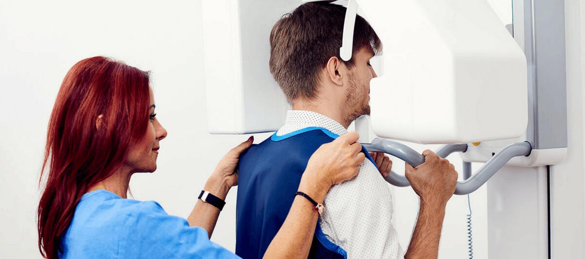 Az Artdent fogászat asszisztense segít ráadni a páciense az ólommellényt panoráma fogröntgen előtt.
