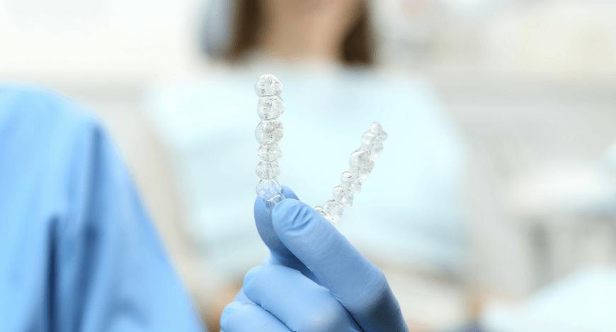Dr. Friedreich Dóra, az Artdent fogszabályozó szakorvosa egy láthatatlan fogszabályozó készüléket tart a kezében a budapesti fogászati rendelőben.
