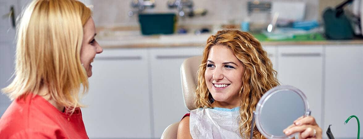 Dr. Friedreich Dóra, az Artdent fogszabályozó szakorvosa és a páciens egymásra néz és mosolyog a fogszabályozás után.