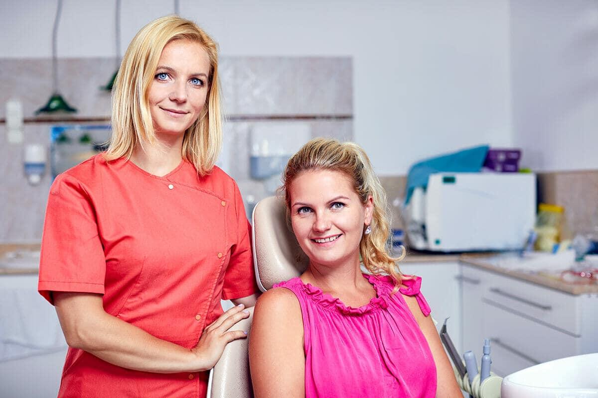 Dr. Friedreich Dóra, az Artdent fogszabályozó szakorvosa és a páciense egymás mellett állnak és mosolyognak a fogszabályozást megelőző konzultáció után.