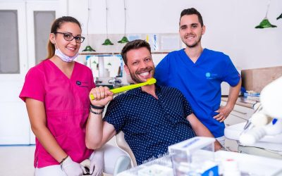 Az esztétikus fogtömés után Dr. Ökrös Petra fogorvos, Dr. Varajti Artúr szájsebész, és páciens mosolyognak.