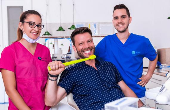 Dr. Varajti Artúr, Dr. Ökrös Petra, és az Artdent fogászat egyik páciense áll a budapesti rendelőben. Megmutatják a fogmosás helyes módszerét.