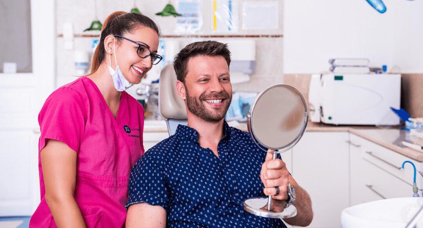 Dr. Ökrös Petra és páciensse az ultahangos fogkőeltávolítás után nézik a tükröt és mosolyognak.