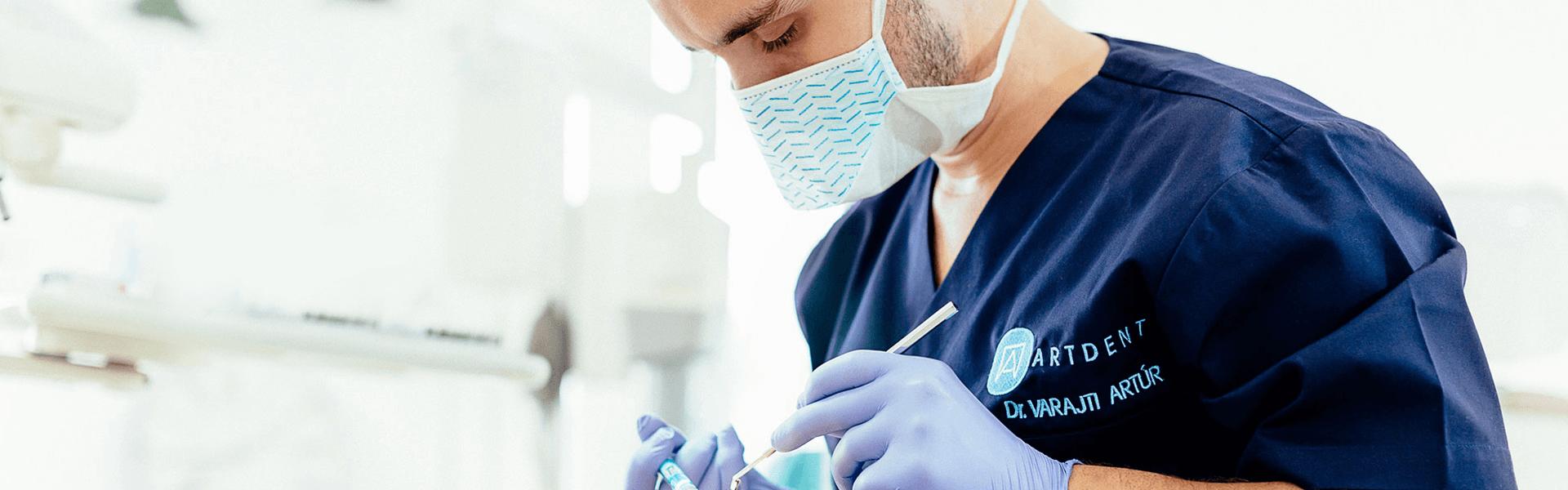 Dr. Varajti Artúr fogorvos, szájsebész érzéstelenítőt ad a pácienst a budapesti fogászati rendelőben.