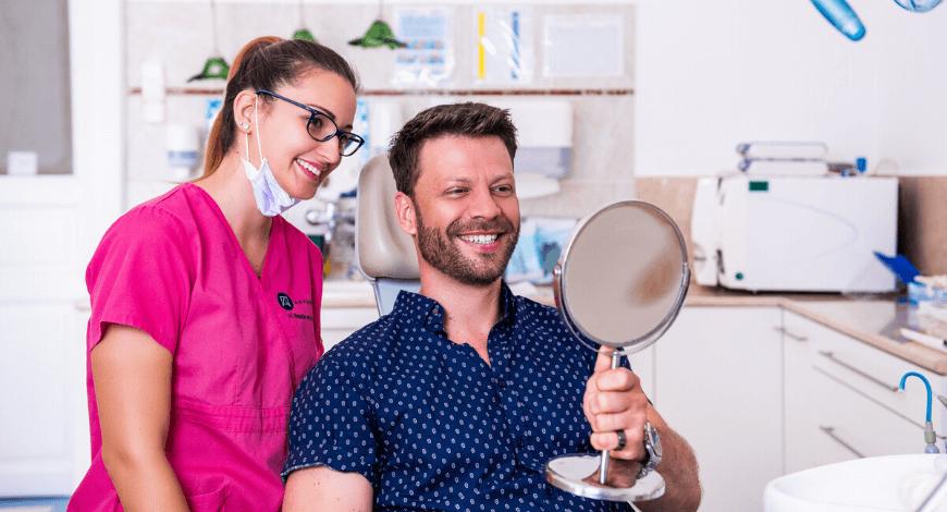 Gyökérkezelés után Dr. Ökrös Petra fogorvos és páciense mosolyog.