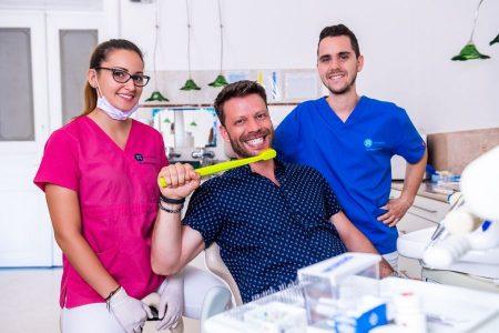 Ultrahangos fogkőeltávolítás után Dr. Varajti Artúr, Dr. Ökrös Petra, és páciensük mosolyognak.